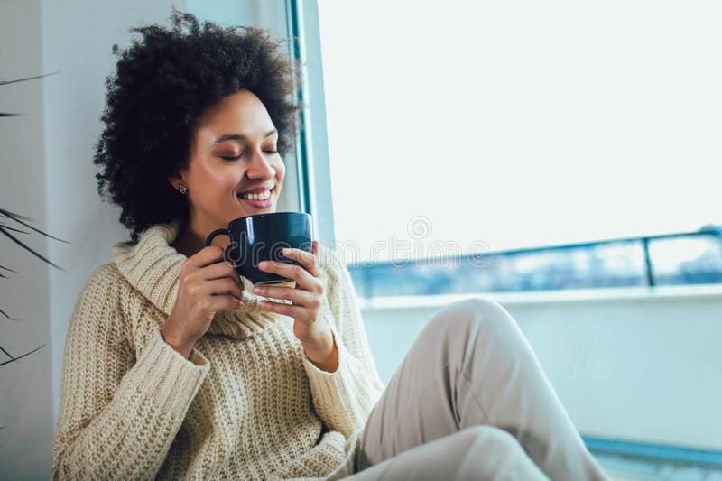 African American woman in her living room drinking holding a coffee mug stock image
