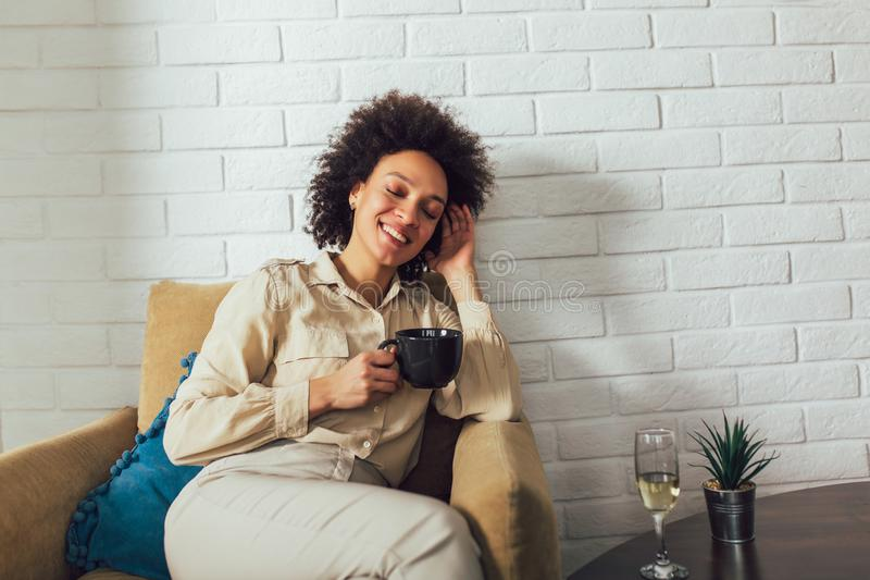 African American woman in her living room drinking holding a coffee mug royalty free stock photography