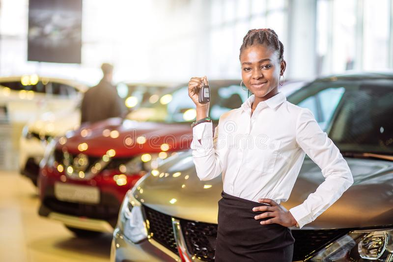 African woman with her new car showing key royalty free stock image