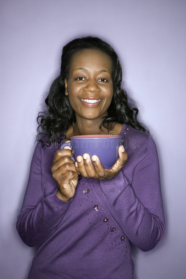 African-American woman holding latte cup. stock photo
