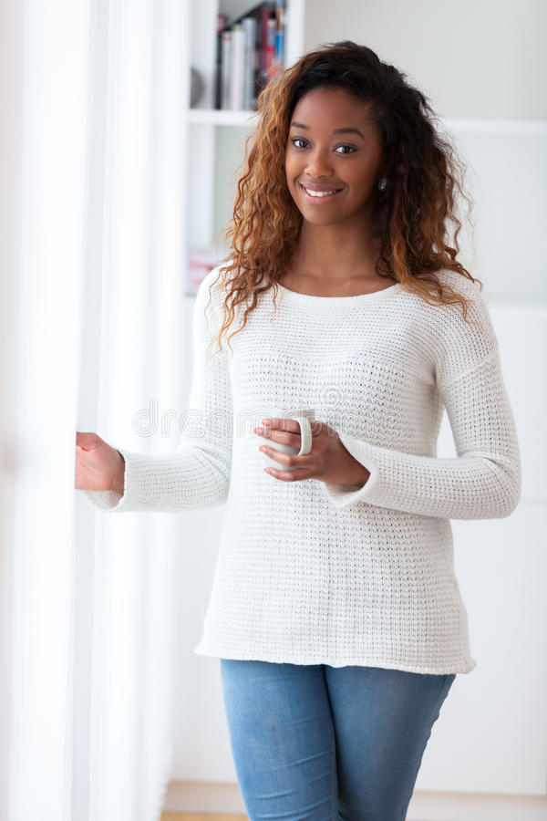 Free African American Woman In Her Living Room Drinking Holding A Coffee Tea Mug - Black People Royalty Free Stock Image - 50437486