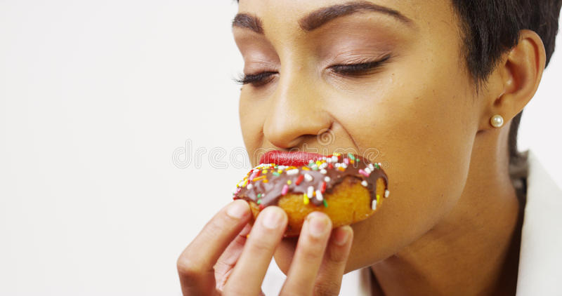 African American woman indulging in delicious chocolate donut stock photography
