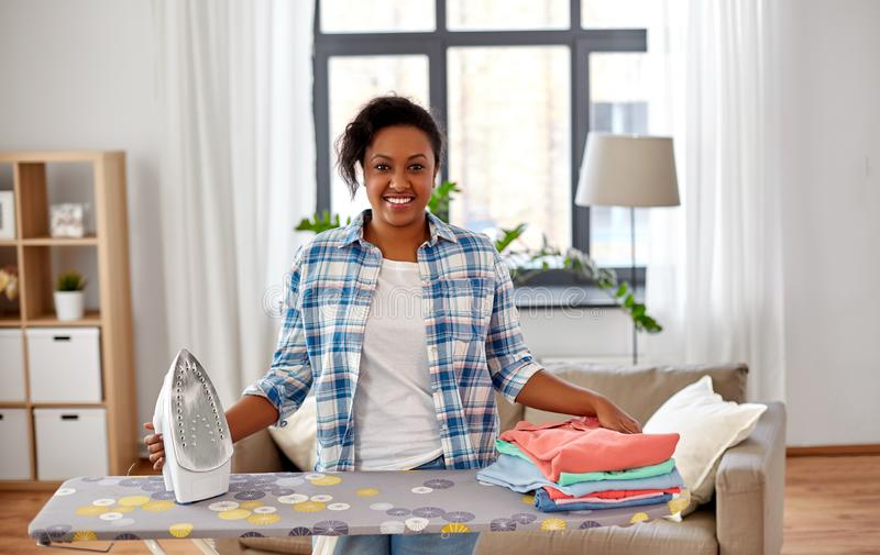 African american woman with ironed clothes at home. Housework, laundry and housekeeping concept - happy african american woman with ironed clothes on iron board royalty free stock photos