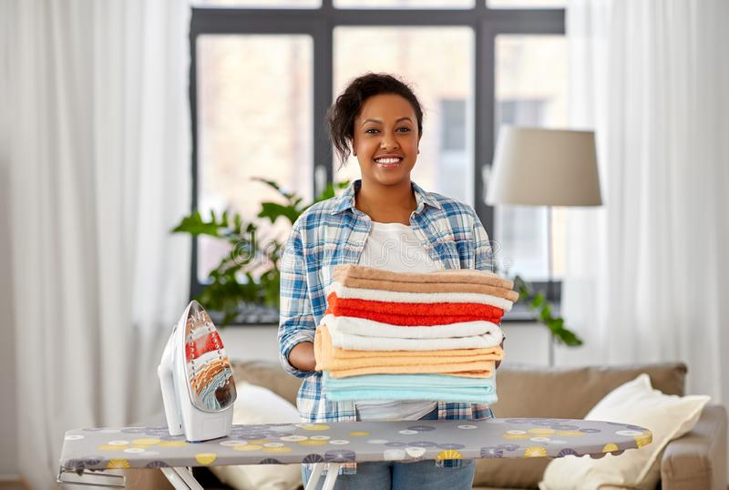 African american woman with ironed linen at home. Housework, laundry and housekeeping concept - happy african american woman with ironed linen and iron board at stock photos