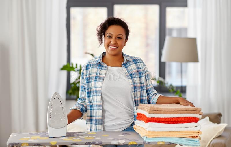African american woman with ironed linen at home. Housework, laundry and housekeeping concept - happy african american woman with ironed linen on iron board at stock photos