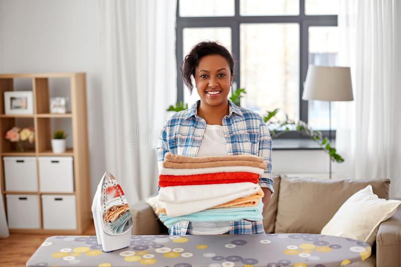 African american woman with ironed linen at home. Housework, laundry and housekeeping concept - happy african american woman with ironed linen and iron board at stock images