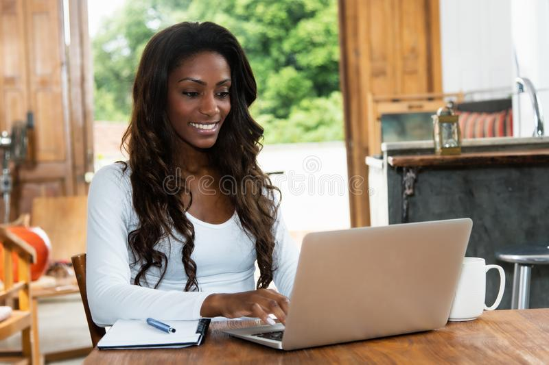African american woman with long hair working at computer stock image