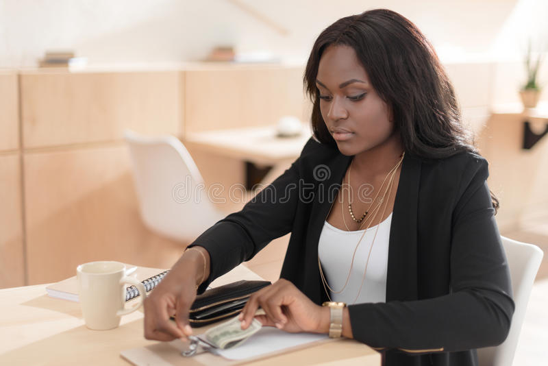 African american woman paying for coffee with cash in cafe. Beautiful african american woman paying for coffee with cash in cafe royalty free stock photography