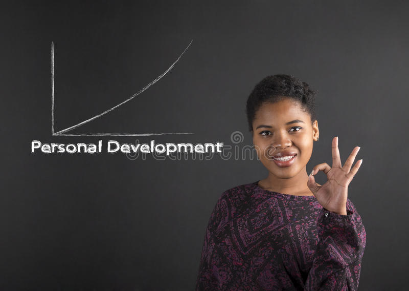 African American woman with perfect hand signal showing personal development on blackboard background stock photography