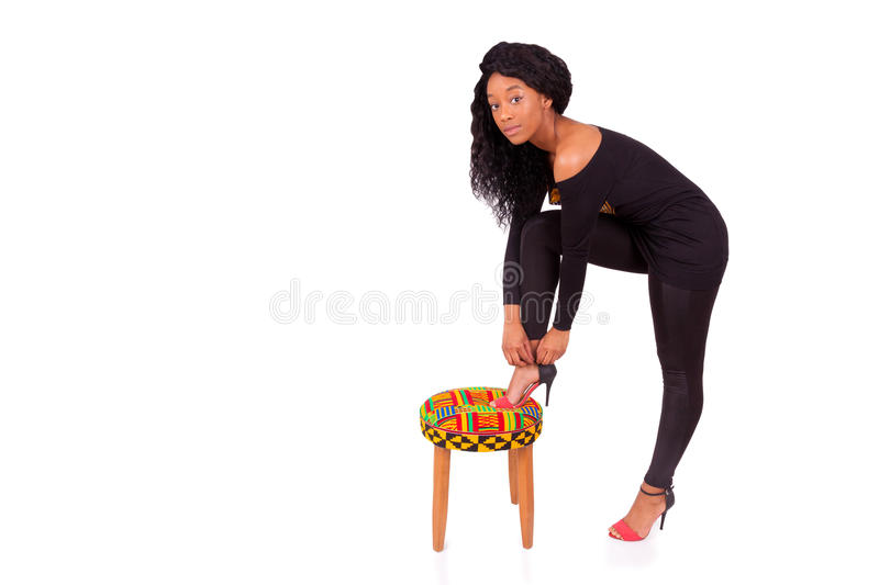 African American woman putting her high heels shoes. Beautiful African American woman putting her high heels shoes royalty free stock photo