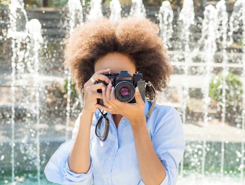 African American Woman Taking Photo With Retro Camera. African american woman with retro camera, female photographer taking photo with vintage camera at summer royalty free stock photo