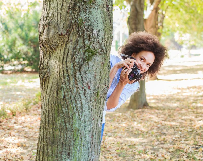 African American Woman With Retro Camera In Nature. African american woman taking photo in nature with old retro camera , female photographer fun outdoor stock photography