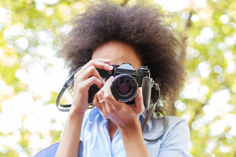 African American Woman With Retro Camera In Nature. African american woman taking photo in nature with old retro camera , female photographer fun outdoor stock image