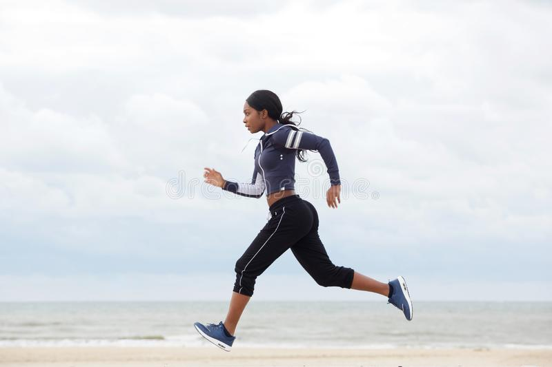 African american woman running by the beach royalty free stock photography