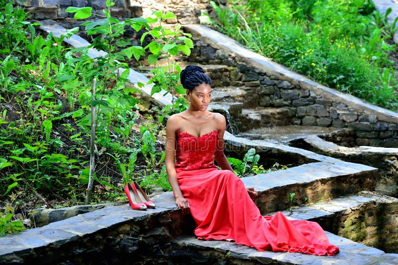 African American woman sitting in the Park posing against the backdrop of green plants on the rocks in a red dress with dreadlocks royalty free stock photos