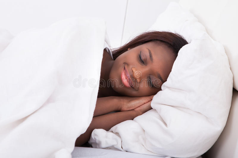 African american woman sleeping in bed stock photos
