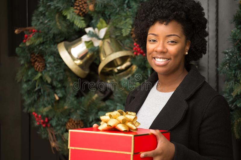 African American woman smiling holding a gift outside. stock photo