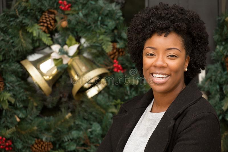 African American woman smiling outside at Christmas. stock photo