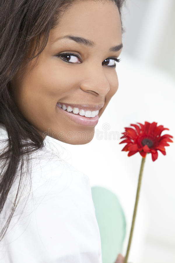 African American Woman Smiling with Red Flower stock image