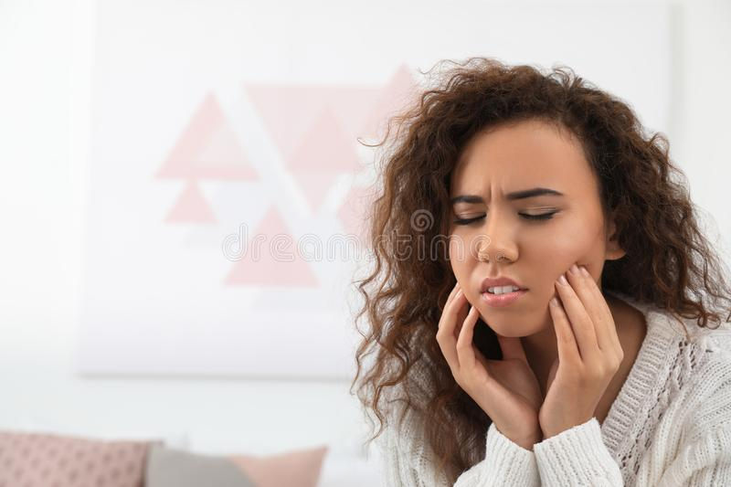 African-American woman suffering from tooth ache. Space for text. African-American woman suffering from tooth ache indoors. Space for text stock photography