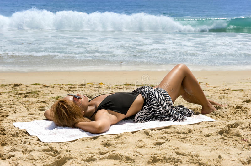 African American woman sunbathing stock photography