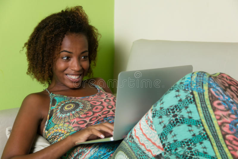 African american woman surfing the net with notebook on couch. At home royalty free stock images