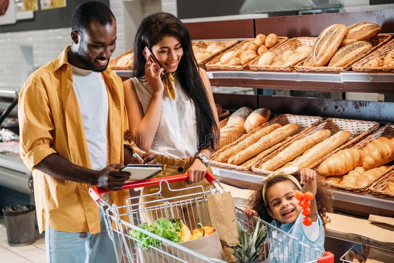 african american woman talking on smartphone while her husband and daughter standing near with shopping trolley stock image