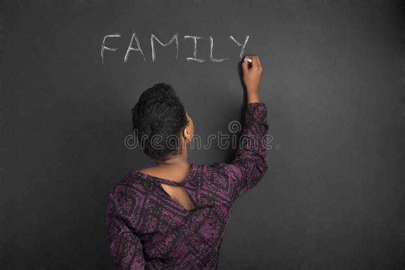 African American woman teacher writing family on chalk black board background stock images