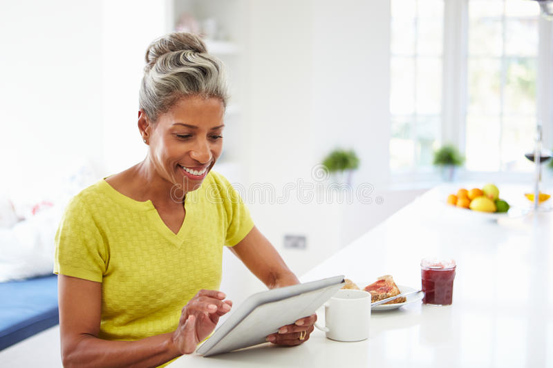 African American Woman Using Digital Tablet At Home stock image