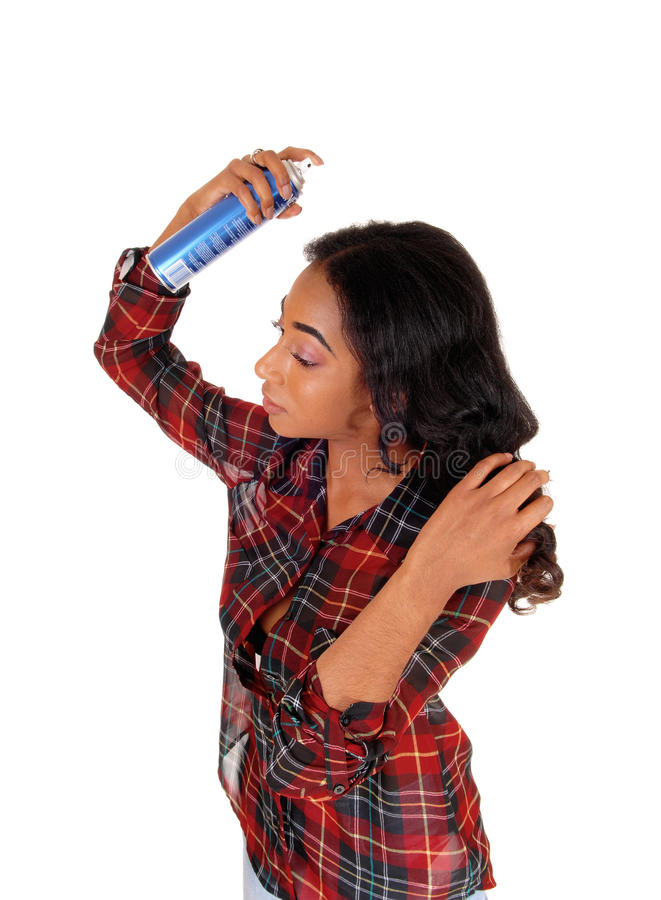 African american woman using hair spray. A profile image of a young african american woman in a colorful shirt spraying hair spray on her hair, isolated for stock photography