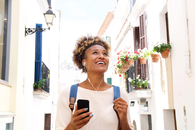 African american woman walking down the street and listening to music on mobile phone. Portrait of african american woman walking down the street and listening stock images