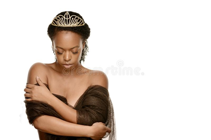 African American woman wearing a golden crown clean face and glowing skin beauty hair and wellness stock photo