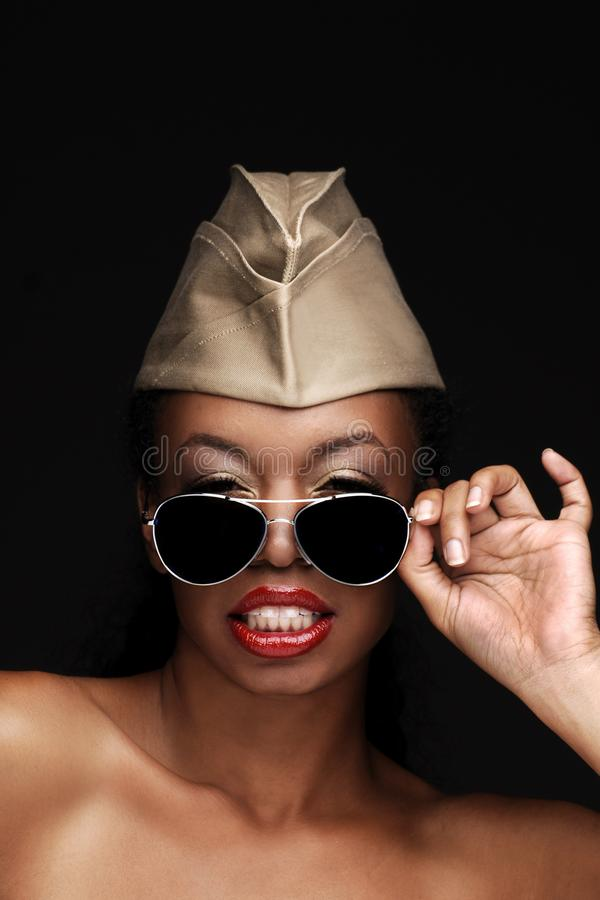 African American woman wearing a military cap and sunglasses with lots of attitude, Beauty model for cosmetic makeup treatments stock photography