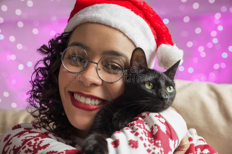 African American woman wearing Santa hat and adorable pet cat. f stock image