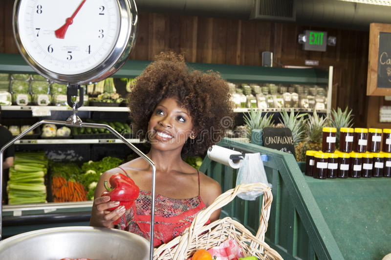 African American woman weighing bell peppers on scale at supermarket. African American women weighing bell peppers on scale at supermarket royalty free stock photos