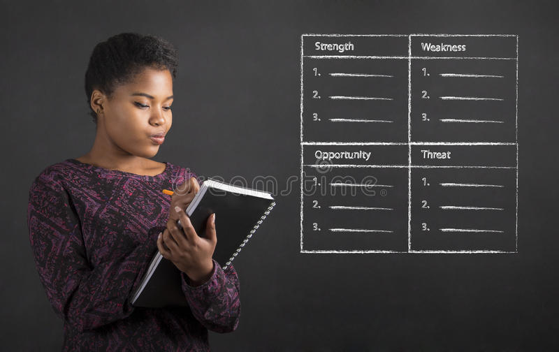 African American woman writing in book diary SWOT analysis on blackboard background stock image