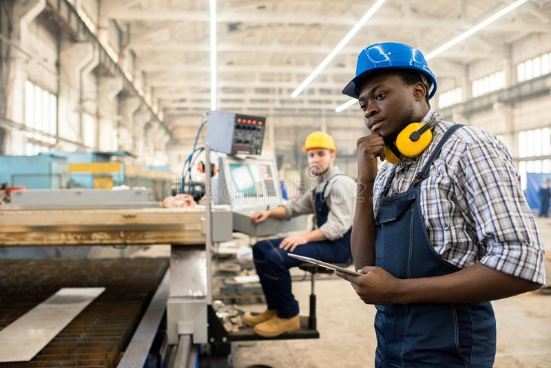 Operating Machine with Digital Tablet. African American worker wearing overall and hardhat operating machine with help of digital tablet, interior of spacious stock images
