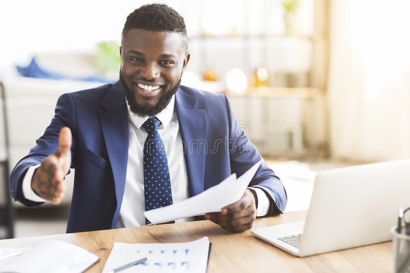 African american young businessman extending hand to shake. Partnership concept. Smiling young african american businessman holding documents and extending hand royalty free stock photography
