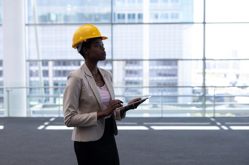 African-American young female architect with digital tablet standing in modern office royalty free stock images