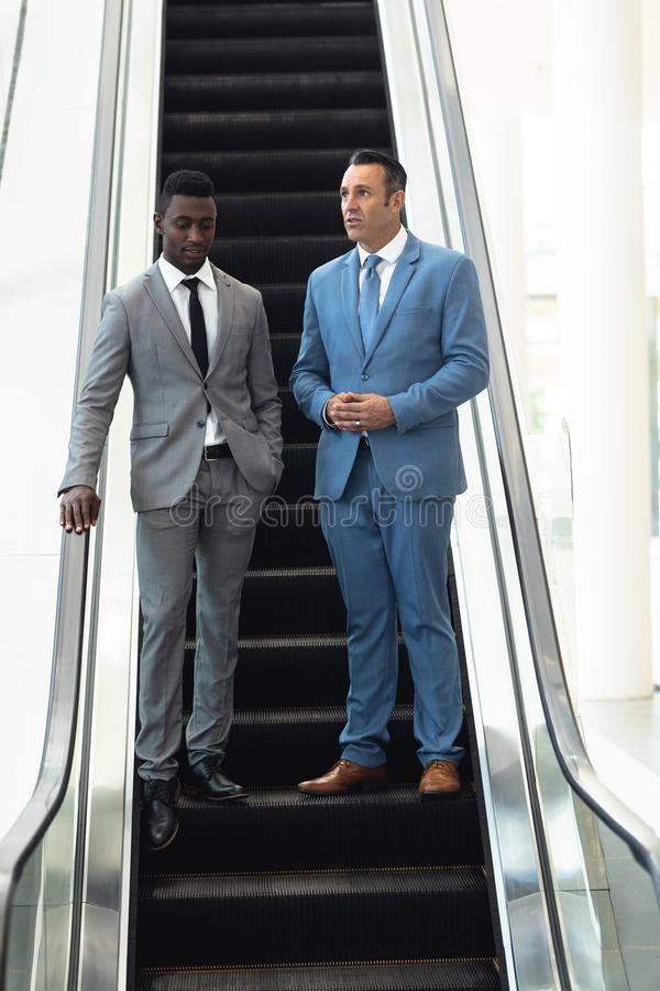 African-american young male executive talking with mature male executive in escalator royalty free stock images