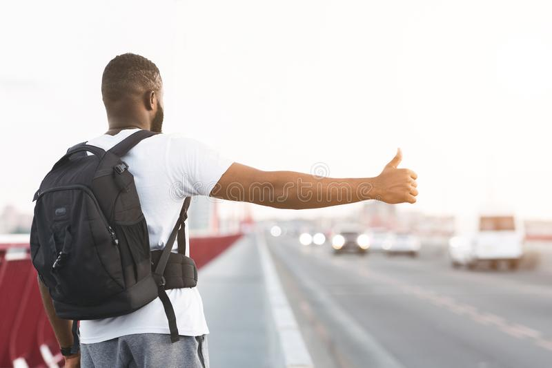 African american young man with backpack hitchhiking royalty free stock photo