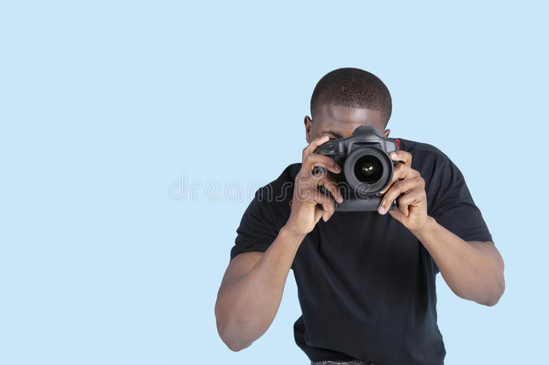 African American young man taking photo through digital camera over blue background royalty free stock photo