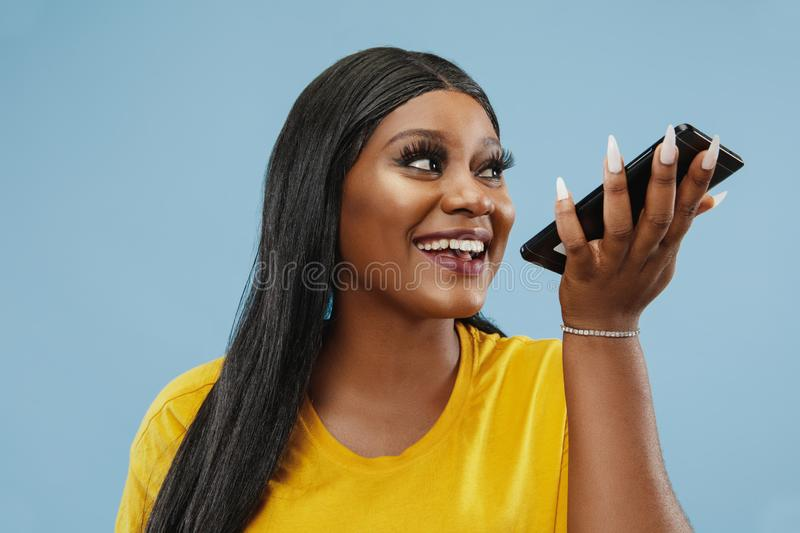 African-american young woman`s half-length portrait on blue background stock images