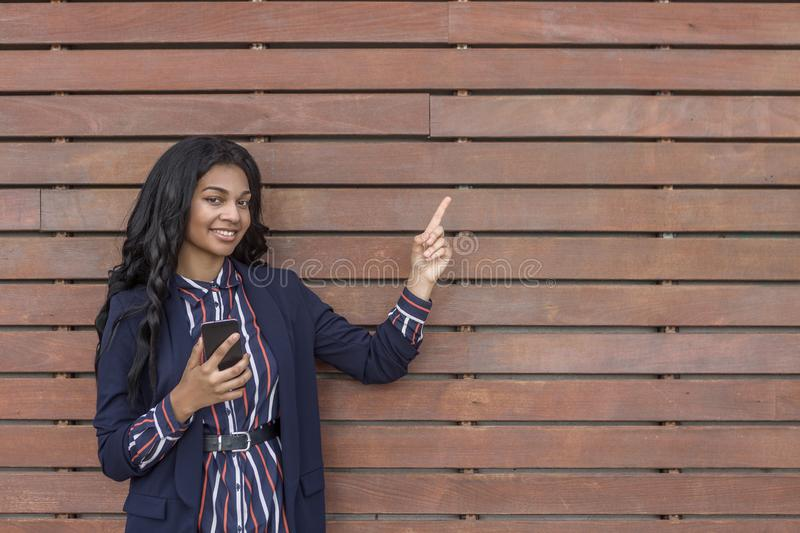 Smiling woman with smart phone pointing copy space stock photos