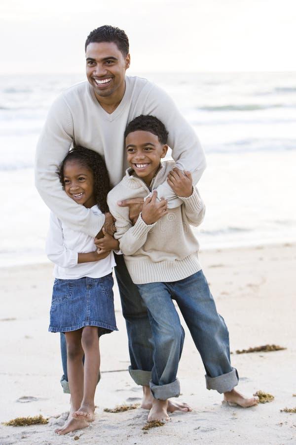 African-Americanvater und zwei Kinder auf Strand lizenzfreies stockfoto