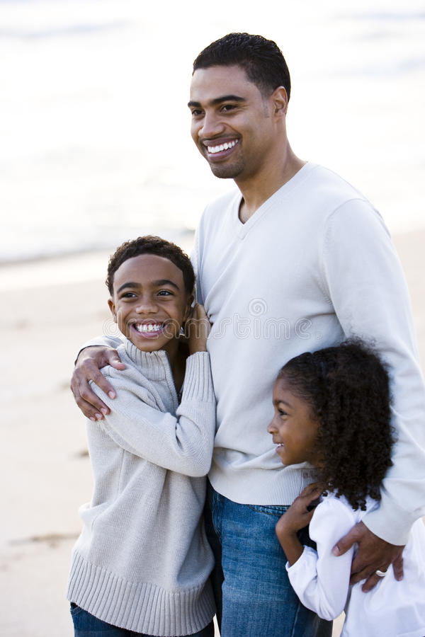 African-Americanvater und zwei Kinder auf Strand lizenzfreies stockbild