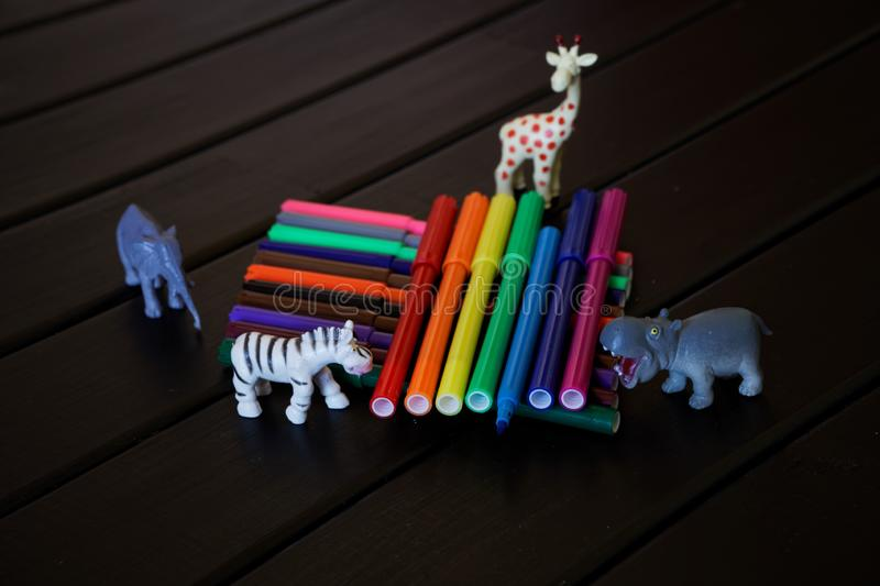 African animals with curiosity look at the multi-colored felt-tip pens. Didactic material royalty free stock photography