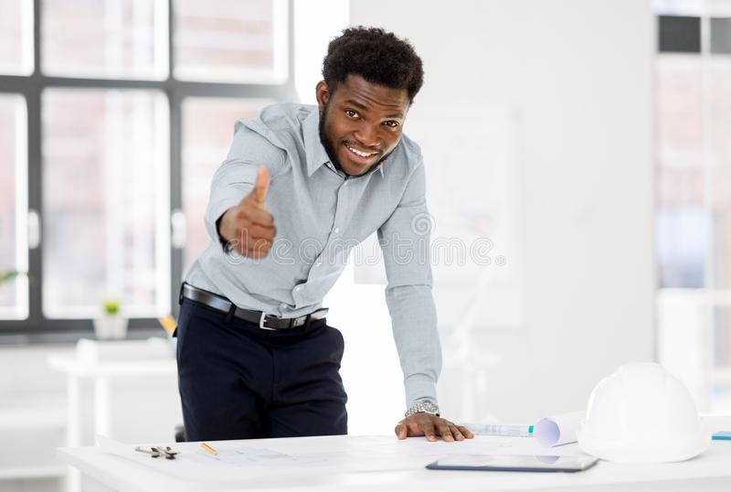 African architect with blueprint showing thumbs up royalty free stock image