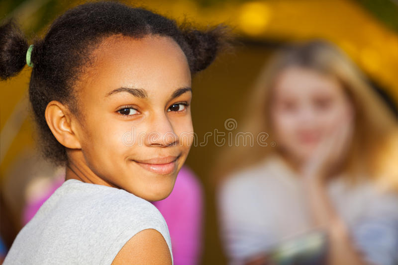 African beautiful girl portrait near yellow tent. Happy African beautiful girl portrait sitting near yellow tent with her friends during sunny autumn day at stock image
