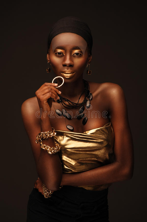 African beautiful woman in gangsta rapper style. With gold make–up and jewelry royalty free stock photography